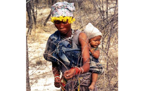 Una madre bosquimana recolecta bayas junto a su bebé en la Reserva de Caza del Kalahari Central, en Botsuana. © Philippe Clotuche/Survival