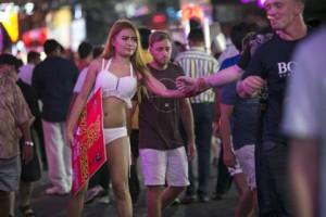 Una mujer que ejerce la prostitución agarra el brazo de un hombre en Pattaya, Tailandia. Paula Bronstein/Getty Images